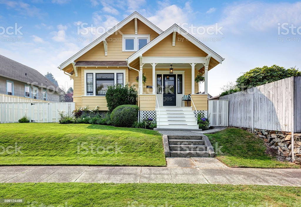 American craftsman home with yellow exterior paint. stock photo