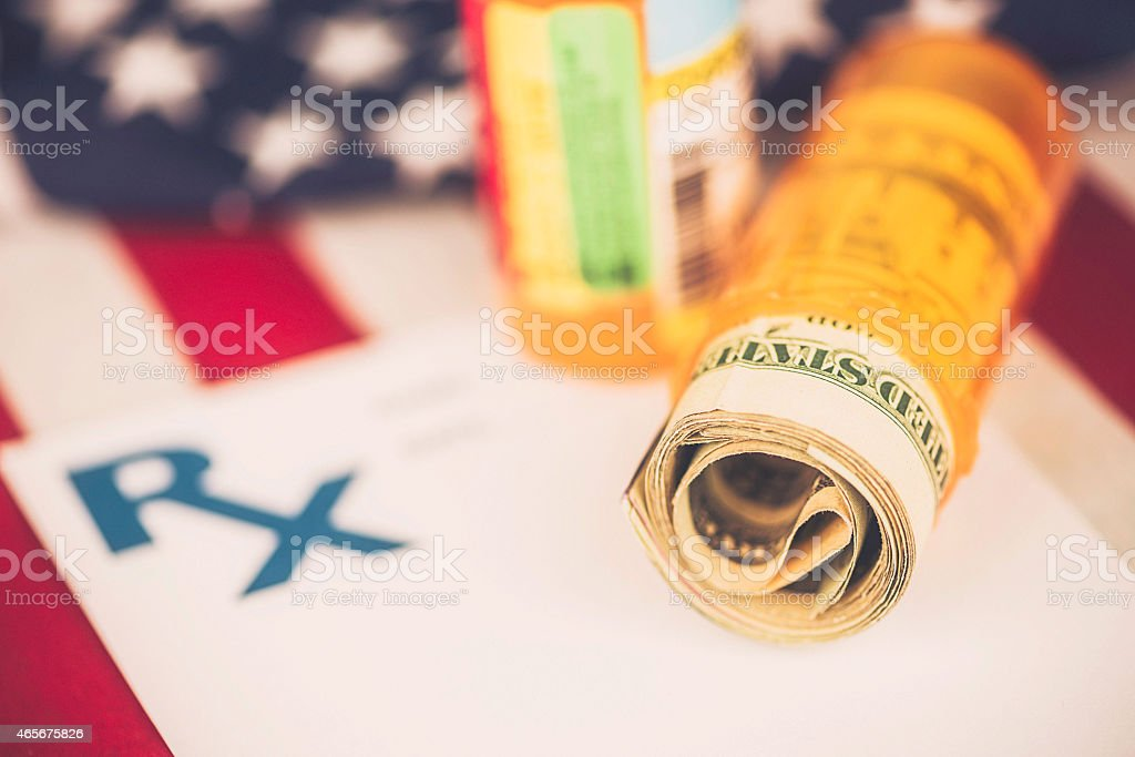 American currency in pill bottle against US flag. Healthcare costs. stock photo