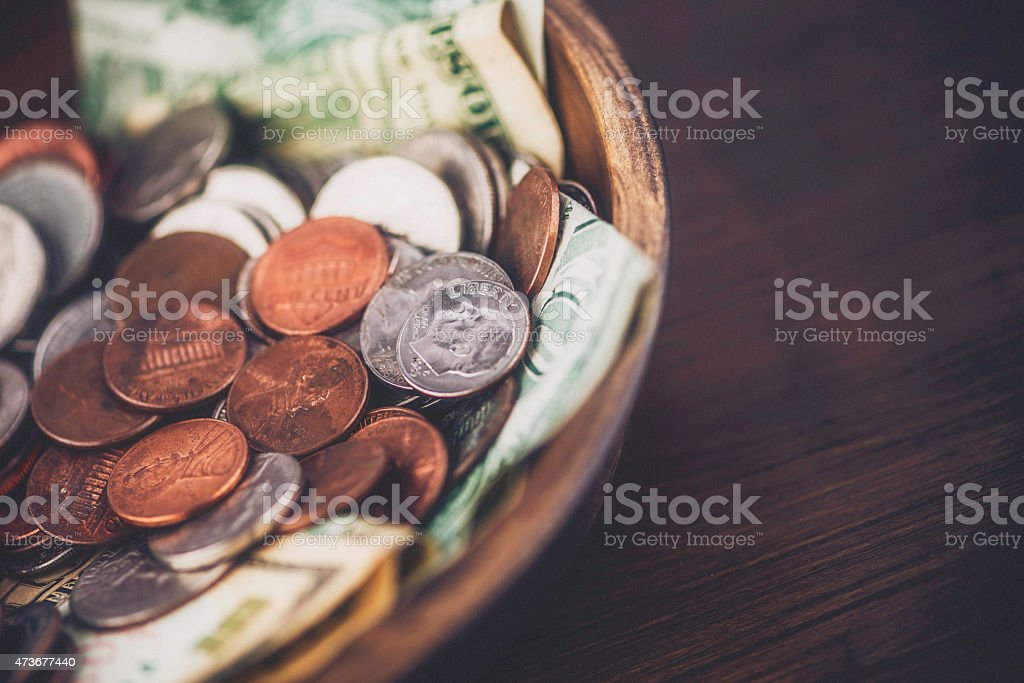American currency wooden collection bowl. Savings. Donations. Bills and coins. stock photo