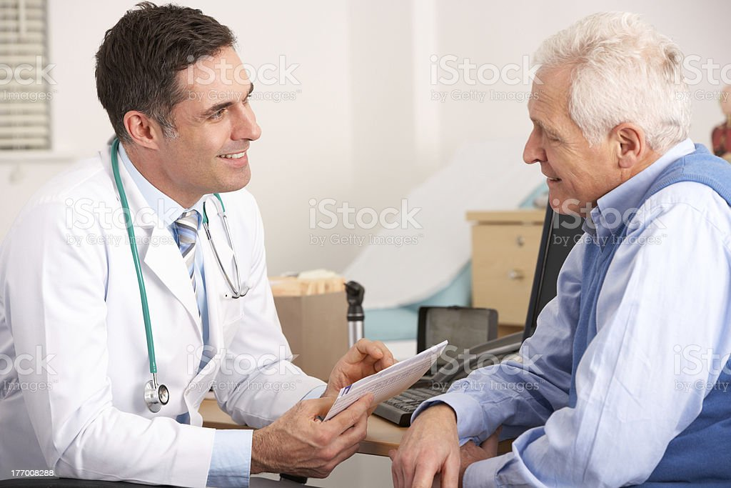 American doctor talking to senior man in surgery stock photo