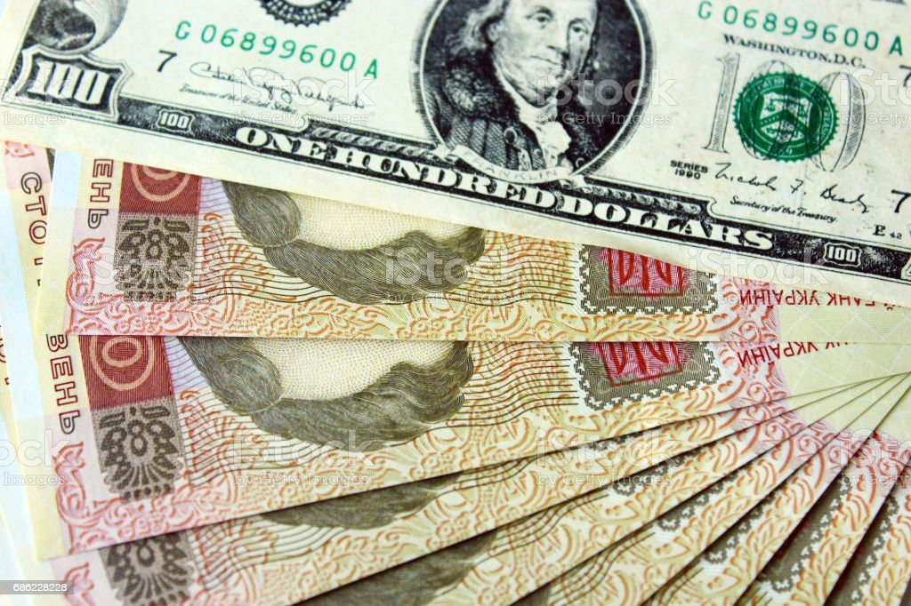 100 American dollars and Ukrainian grivnas banknotes stock photo