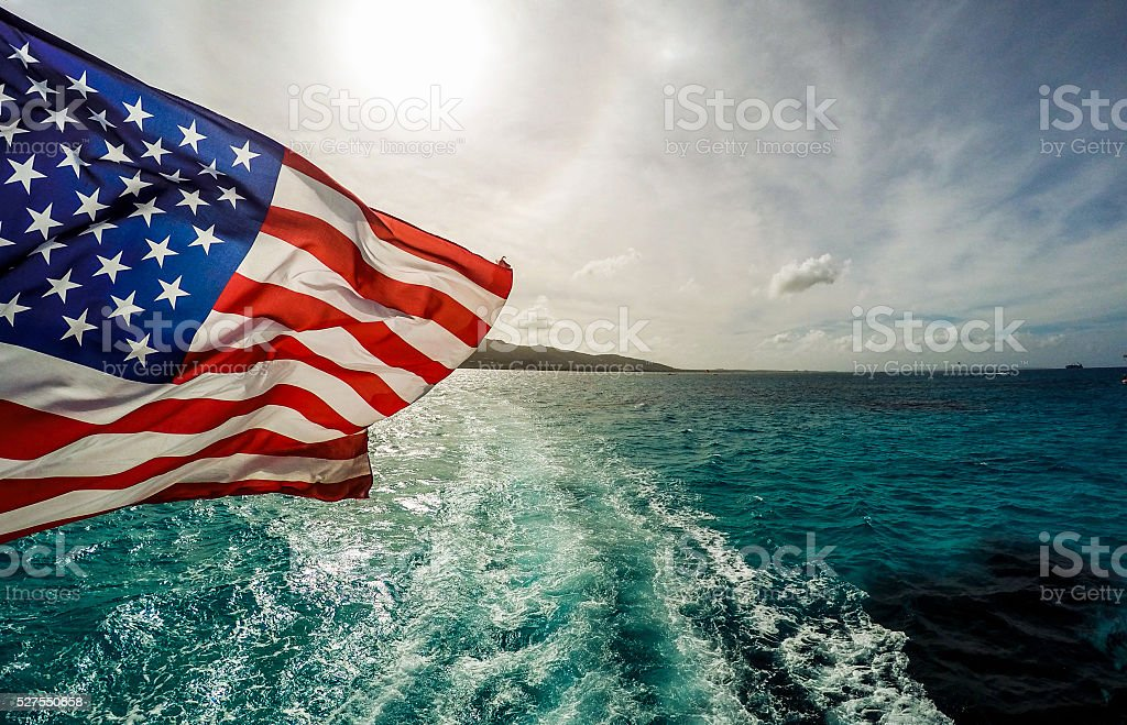 American falg attached to a boat in the sea stock photo