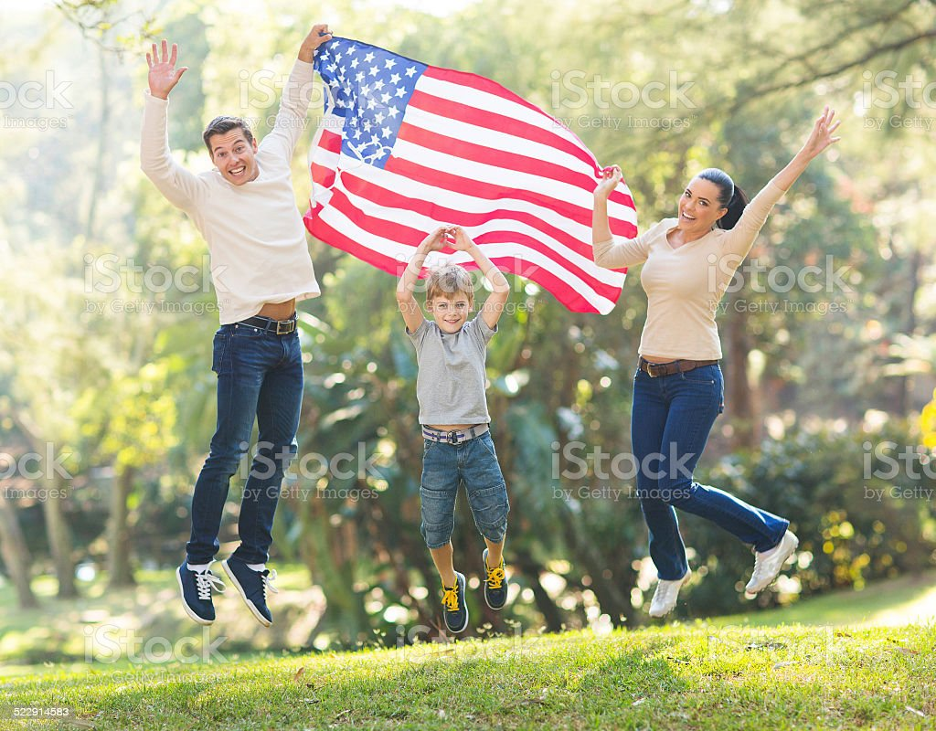 american family jumping with USA flag stock photo