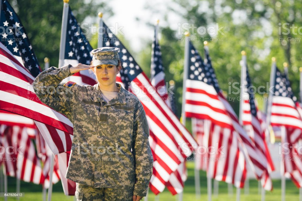 American female soldier saluting in a Field of American Flags stock photo