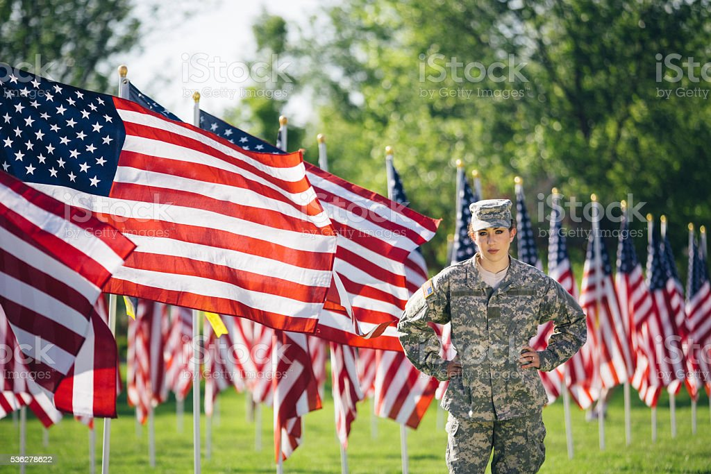 American Female Soldier standing in front of American Flags stock photo