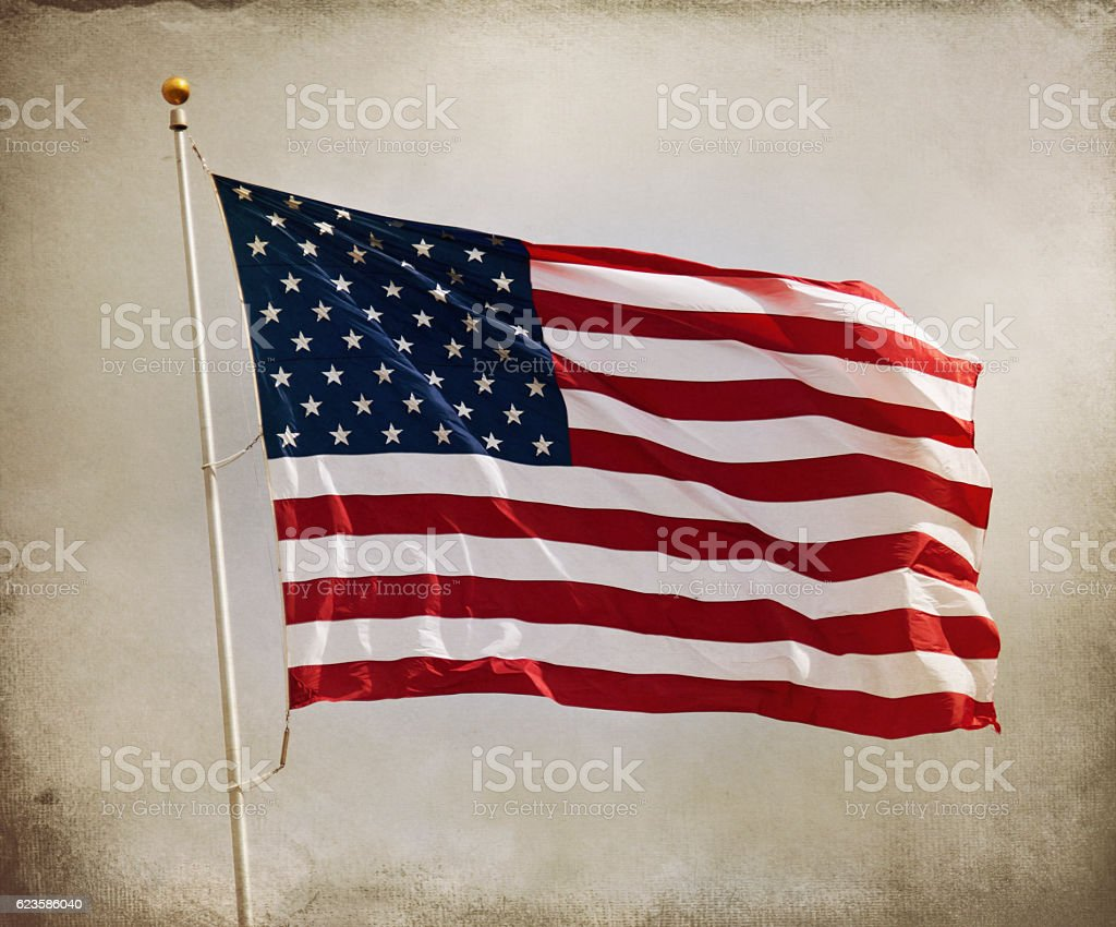 American Flag Against Cloudy Textured and Toned Sunlit Sky stock photo