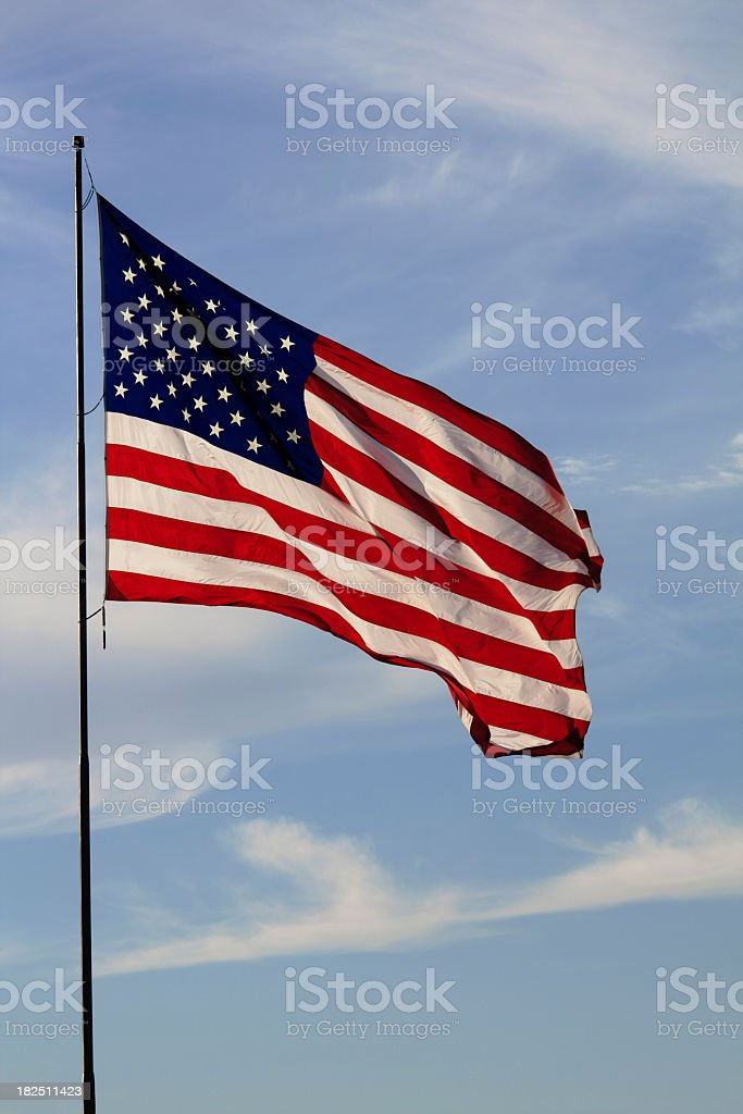 American Flag against pale blue sky with clouds royalty-free stock photo