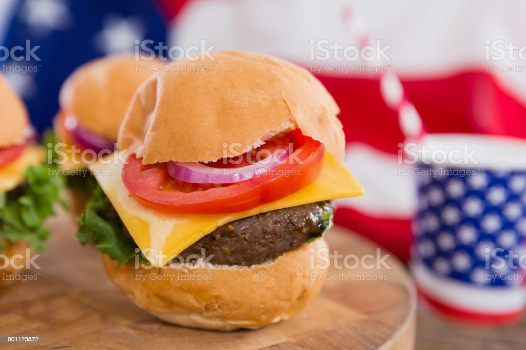 American flag and burgers on wooden table stock photo