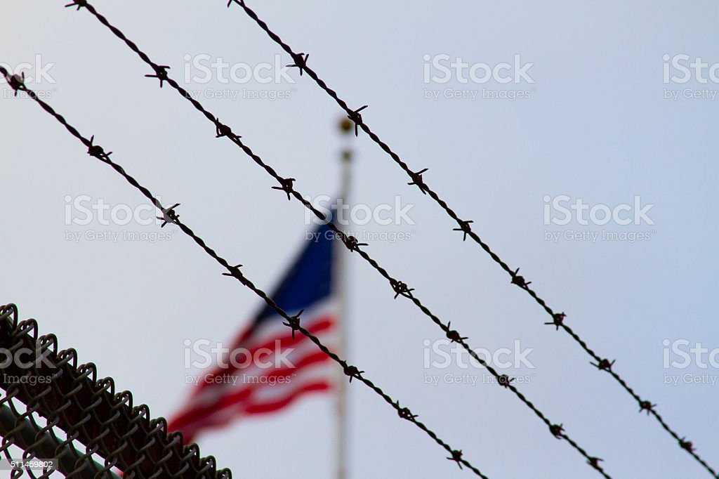 American Flag Behind Barb Wire stock photo