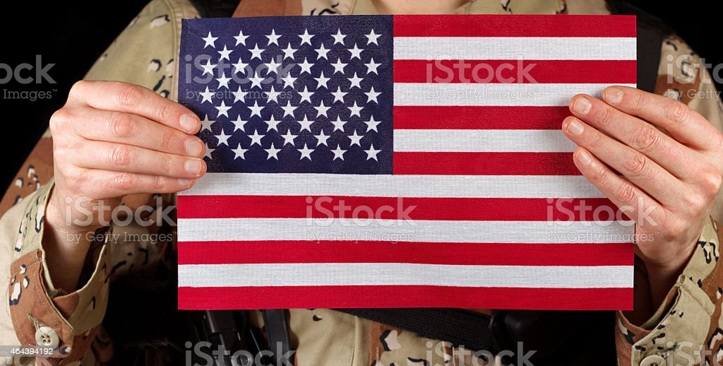 American flag being held by male soldier stock photo