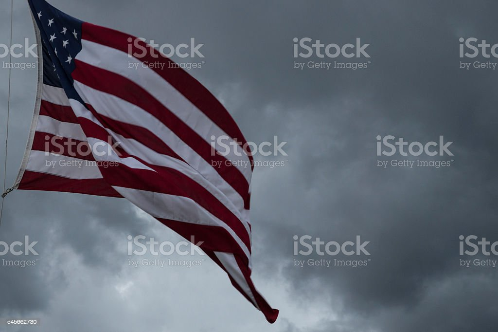 American Flag Blowing During Approaching Storm stock photo