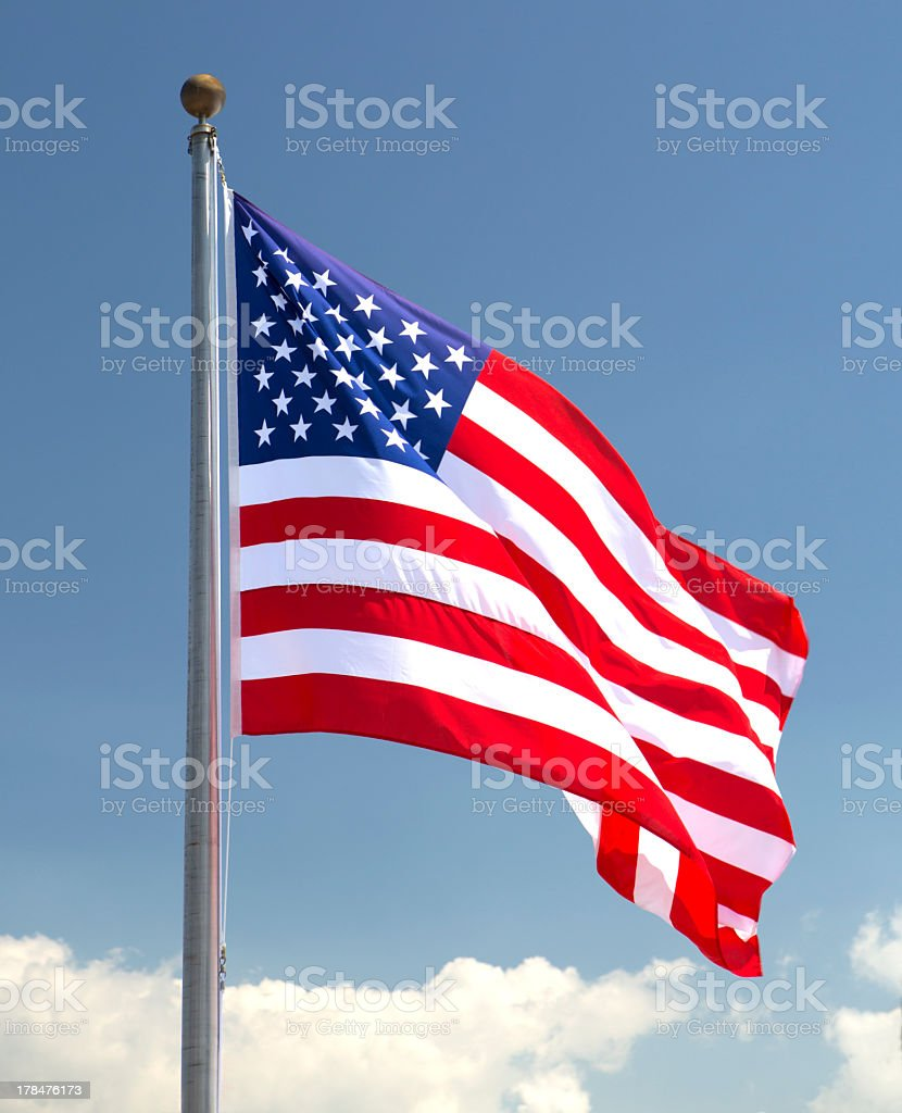 American flag blowing gently in the breeze with blue sky stock photo
