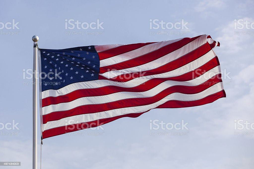 American Flag Blowing in Wind on Blue Sky stock photo
