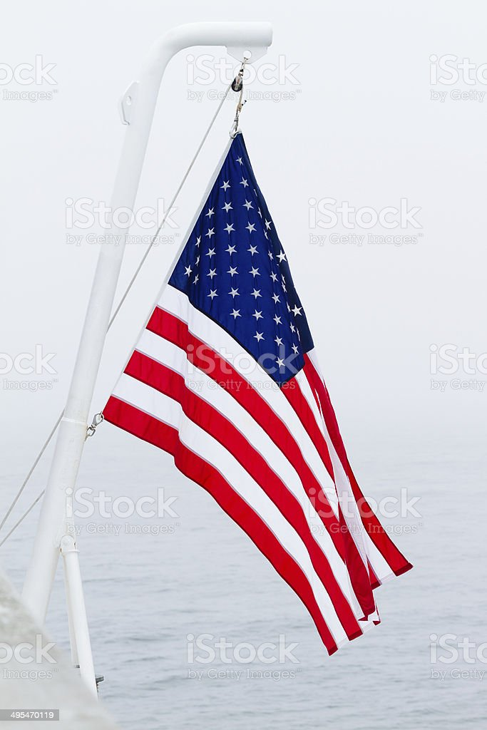 American Flag flies off the stern of a ferry boat. stock photo