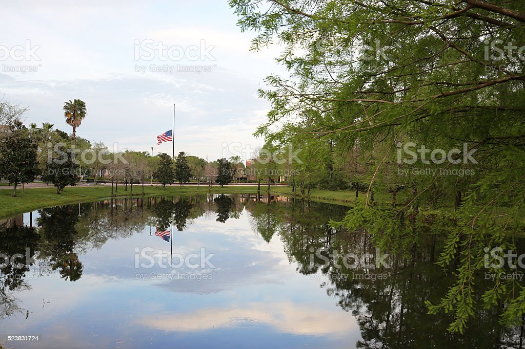 American flag flying at half mast on a university campus stock photo
