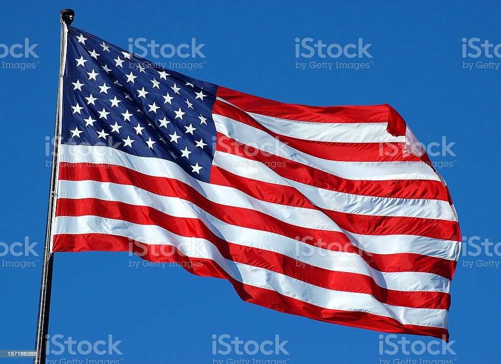 American flag flying high on top of flag pole on a clear day royalty-free stock photo