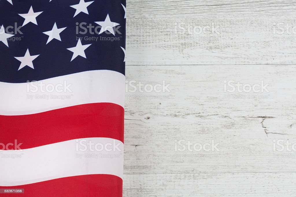 American flag folds on white rustic wood stock photo