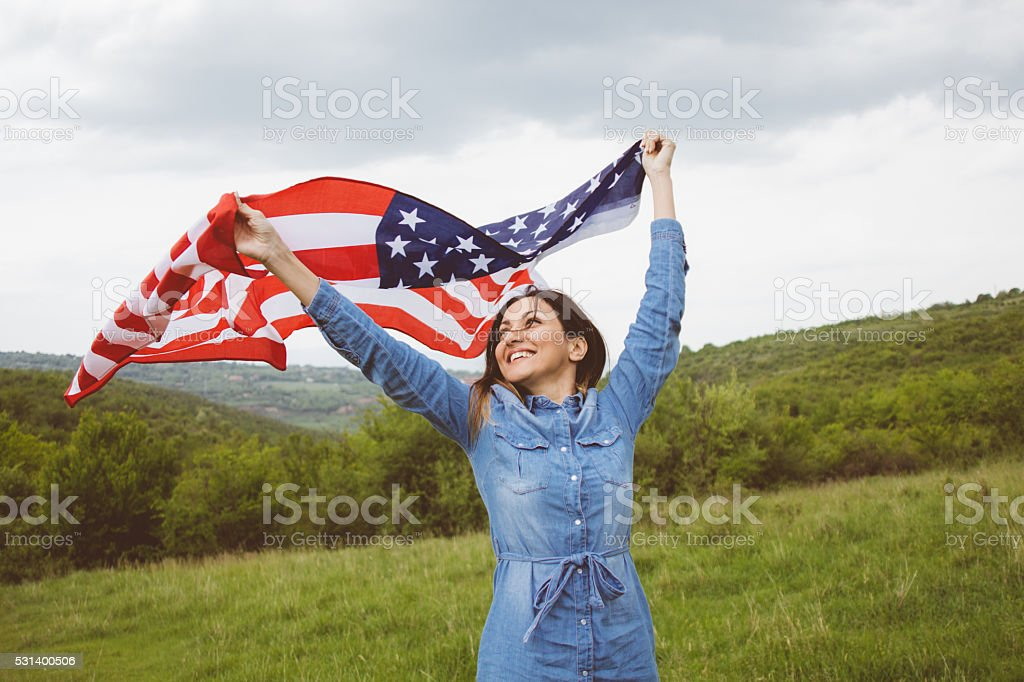 American flag in hands of jolly young woman stock photo