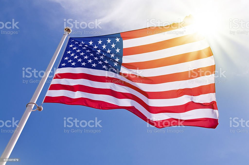 American flag on a pole in a sunny sky stock photo
