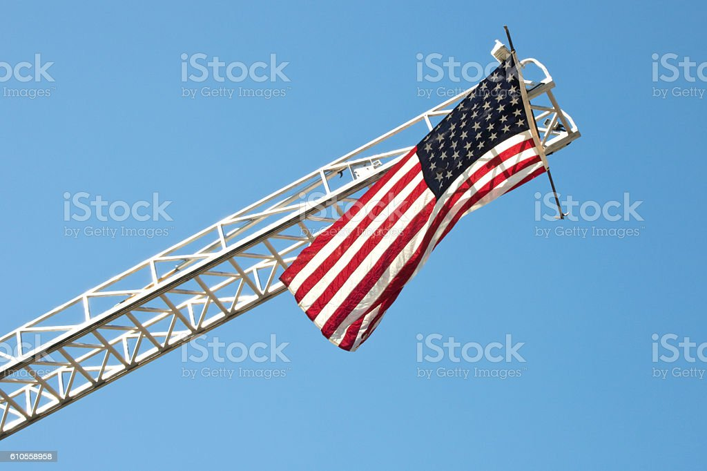 American Flag on Fire Engine Ladder, blue sky background stock photo