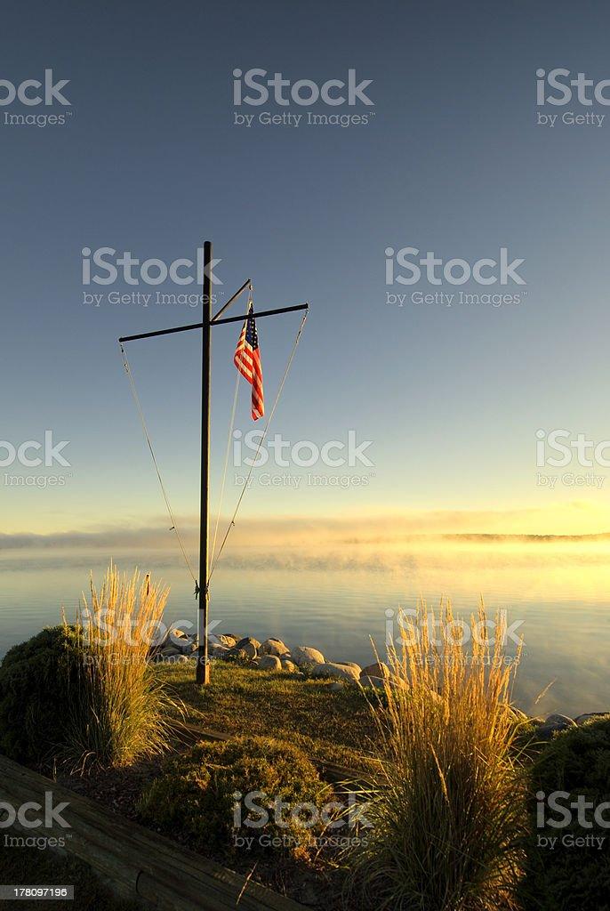 American flag on pole at sunrise beside lake, Minnesota stock photo