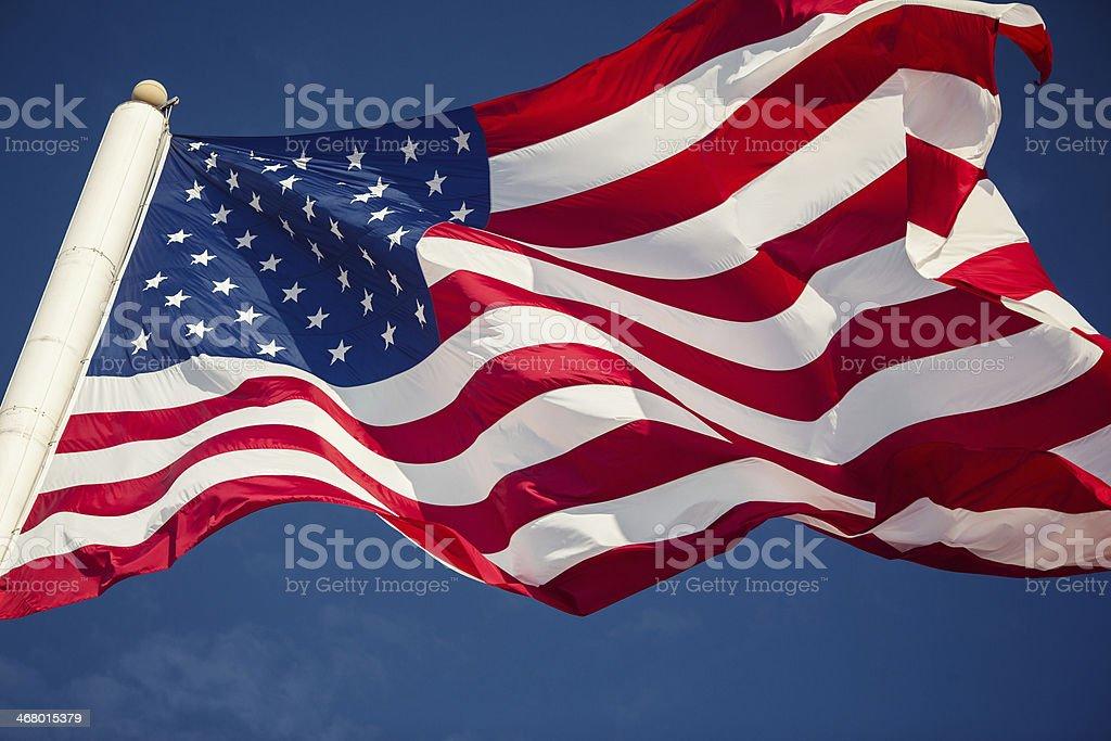 American flag over blue sky stock photo