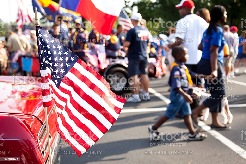 American flag, people in background preparing for parade. stock photo
