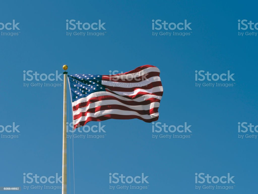 American Flag waving against a blue sky. stock photo