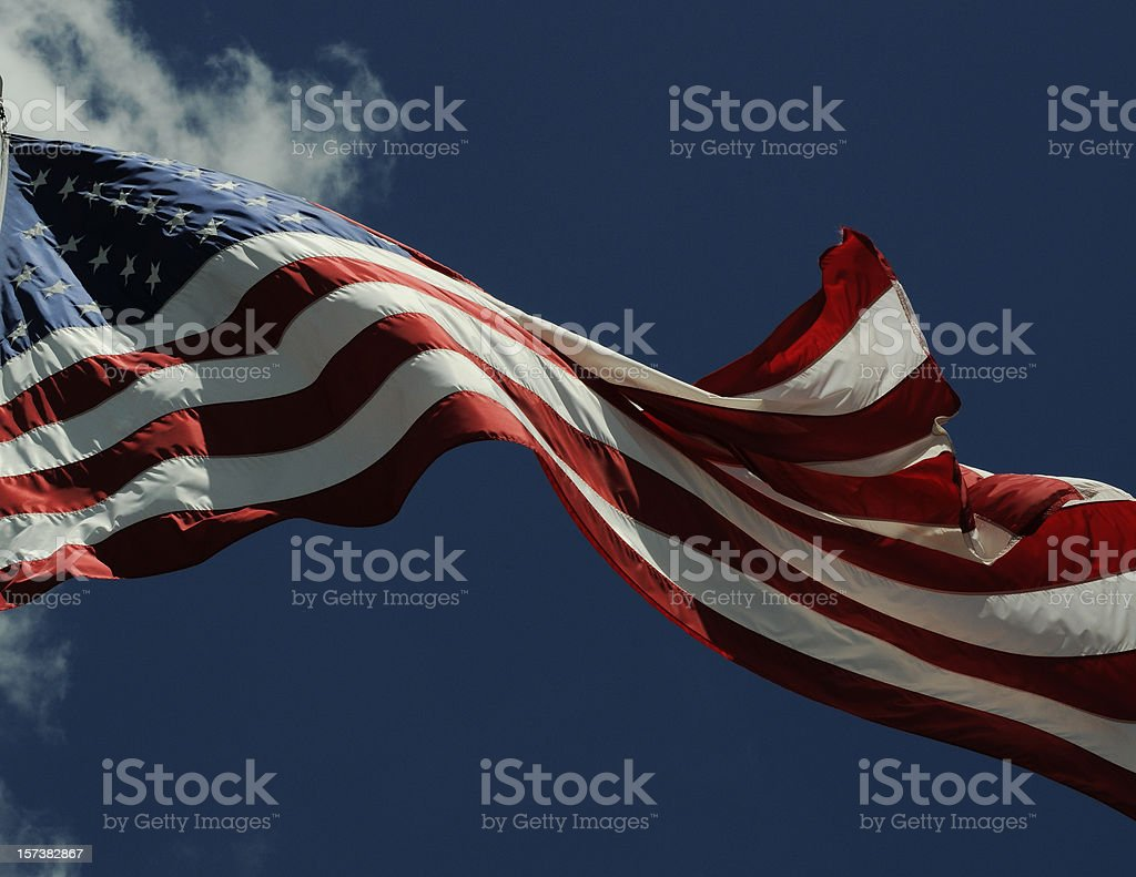 American Flag Waving Against a Dark Blue Sky royalty-free stock photo