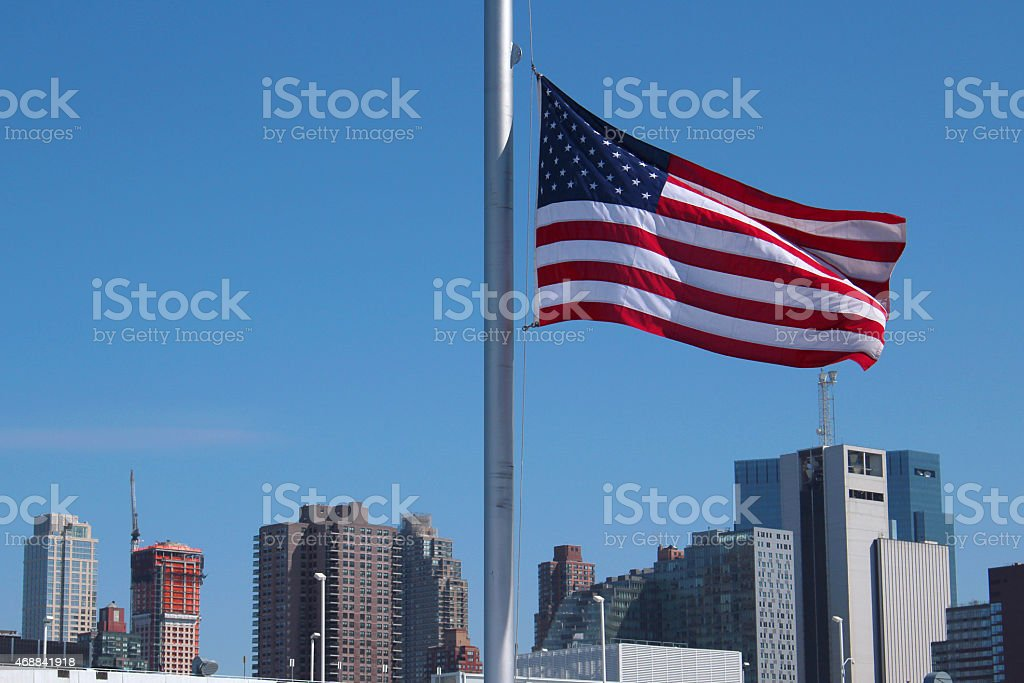 American flag waving and NYC at the back stock photo