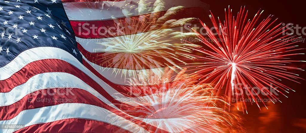 american flag waving for a national holiday with fireworks stock photo