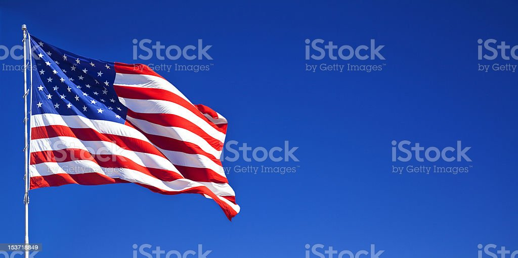 American flag waving in blue sky stock photo