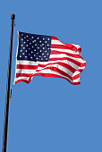 American flag waving in blue sky vertical image