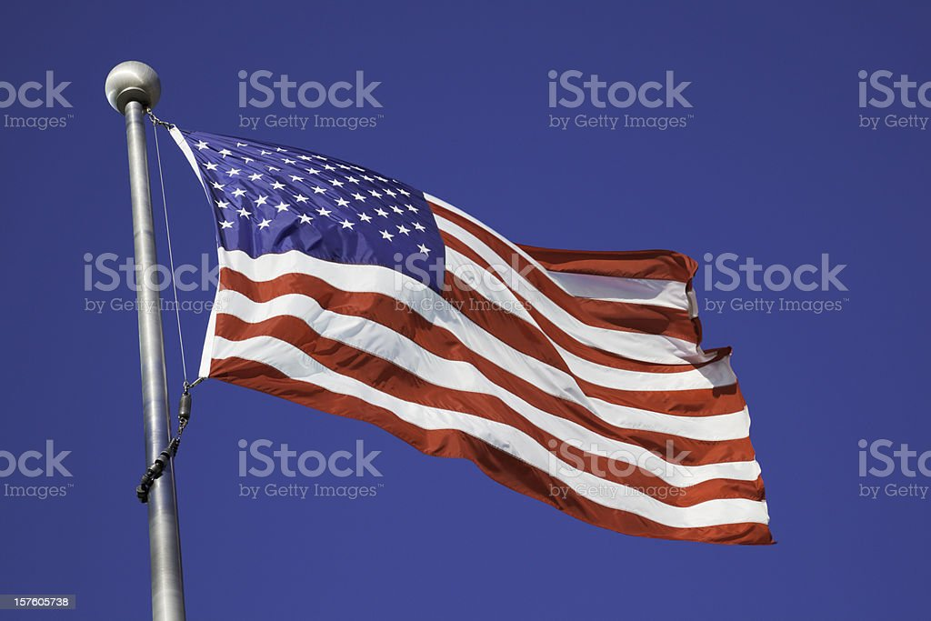 American flag waving in breeze on pole stock photo