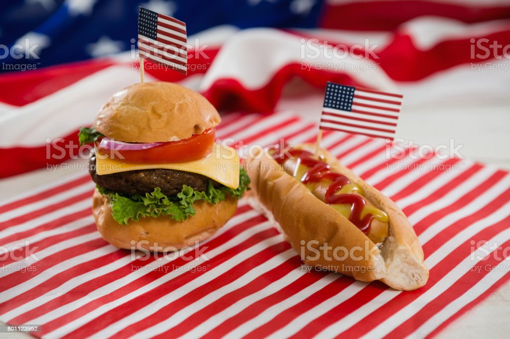 American flag with hot dog and burger on wooden table stock photo