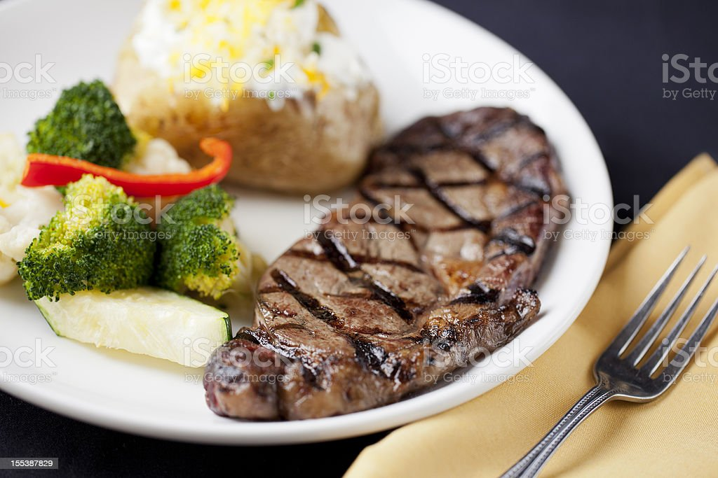 American food: steak with loaded baked potato and vegetables royalty-free stock photo