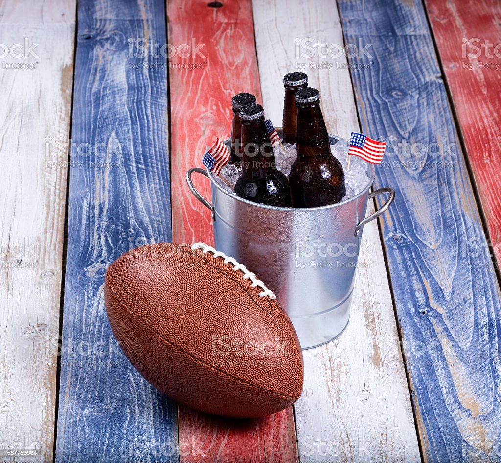 American football and ice cold beer on rustic wooden boards stock photo