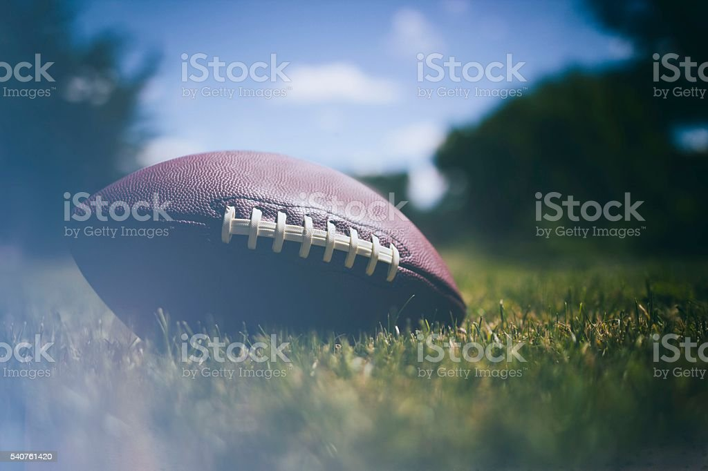 American football ball on grass background stock photo