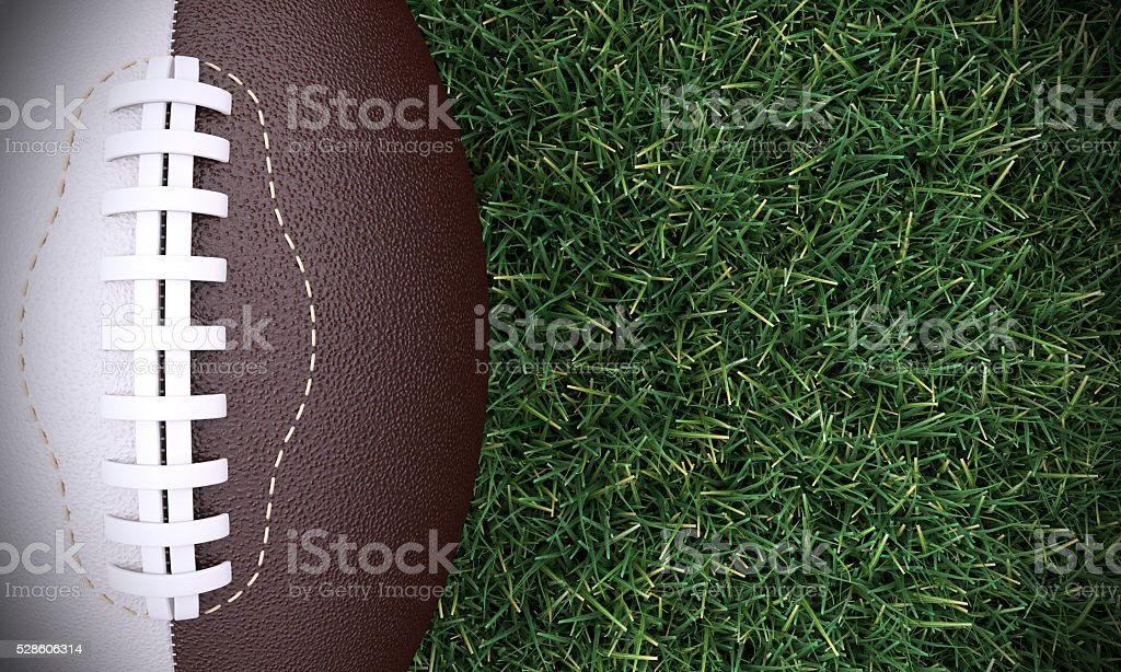 American Football Ball On Realistic Grass stock photo