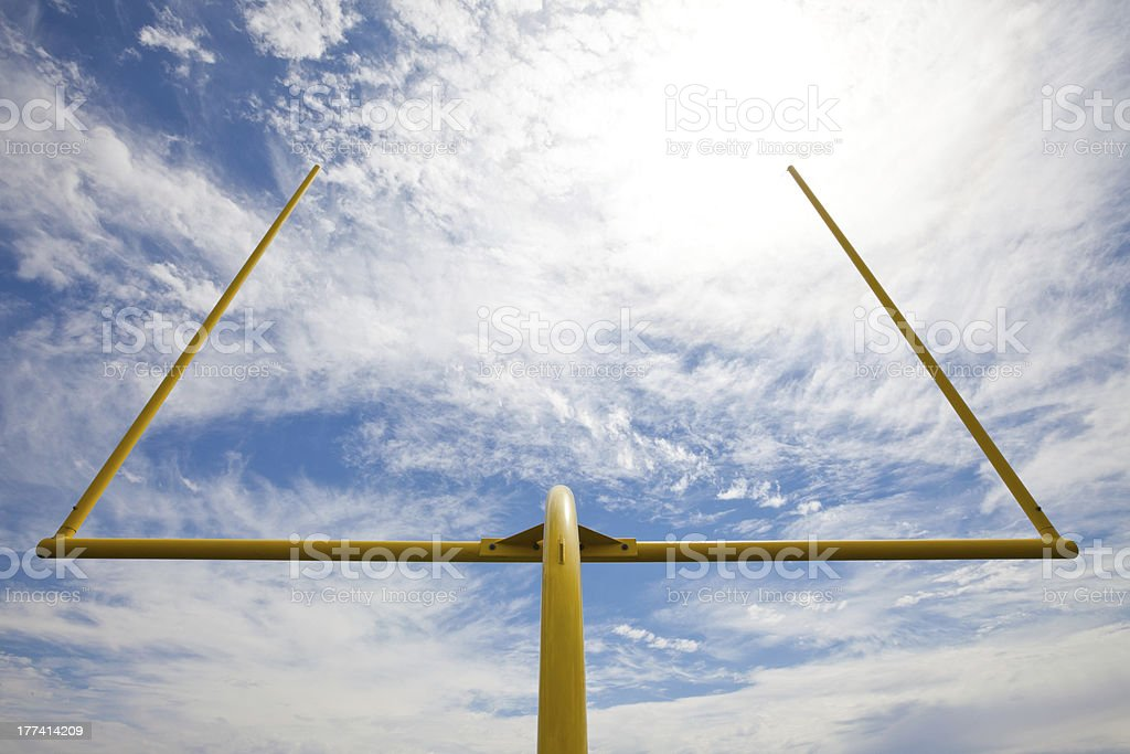 American football goal posts against clouds and blue sky stock photo