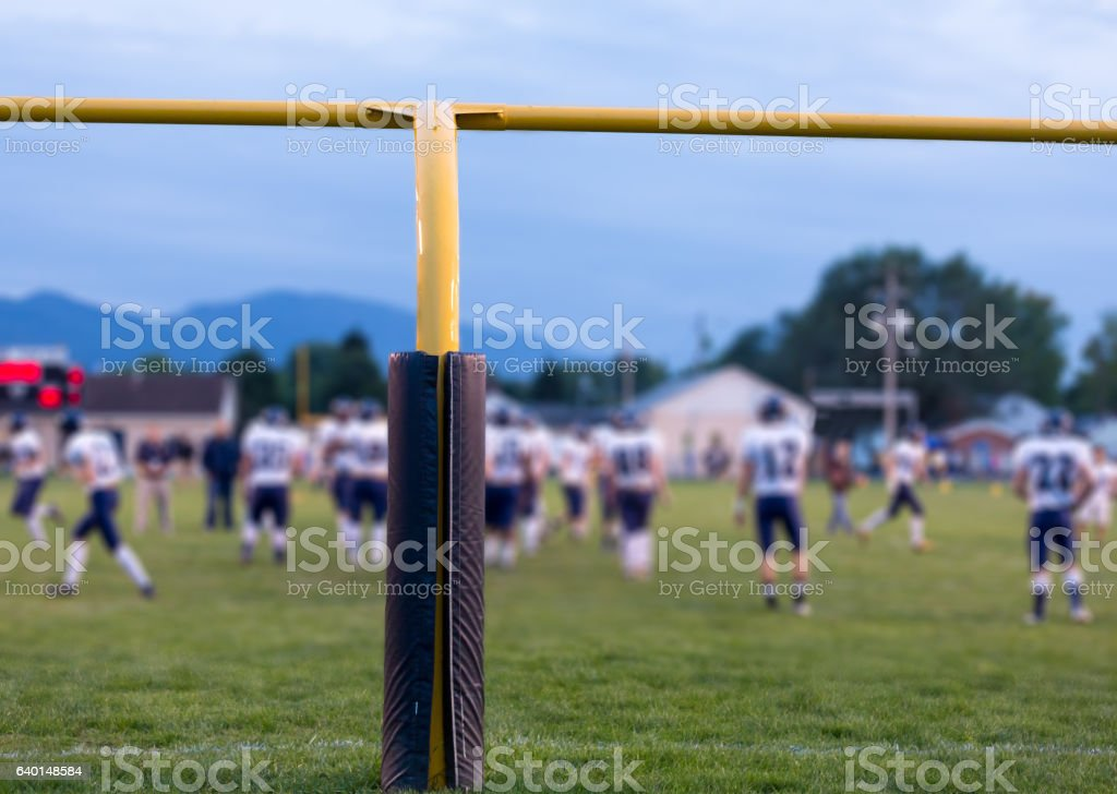 American football goal posts with blurred team stock photo