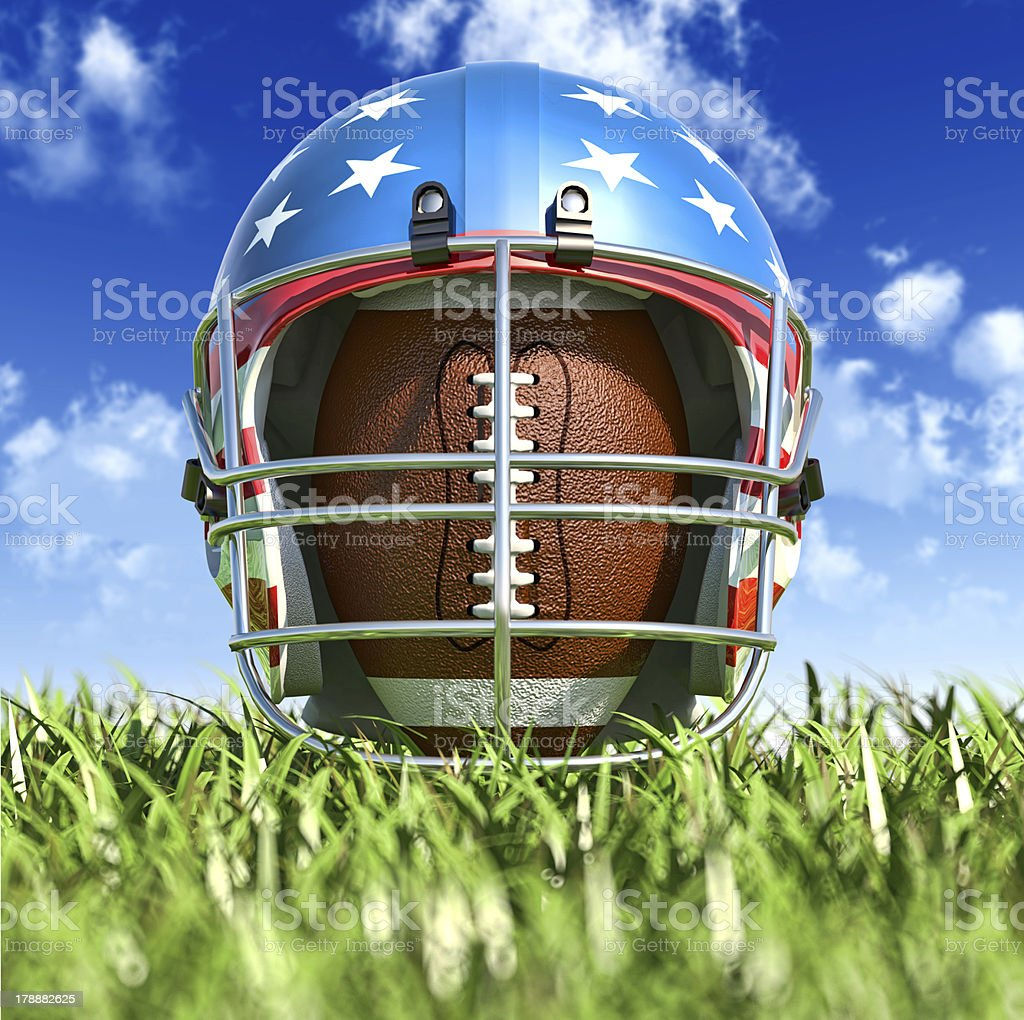American football helmet over the oval ball. Frontal Close-up view. stock photo