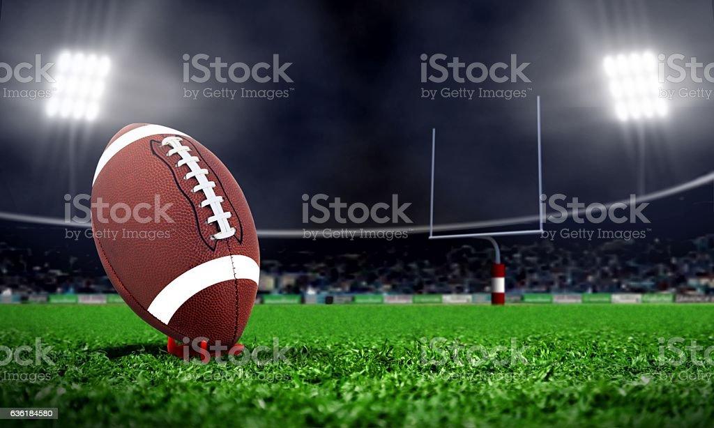 American football in stadium at night with spotlight stock photo