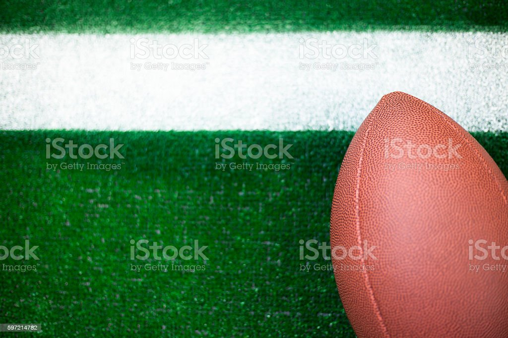 American football on green turf at yard line marker. stock photo