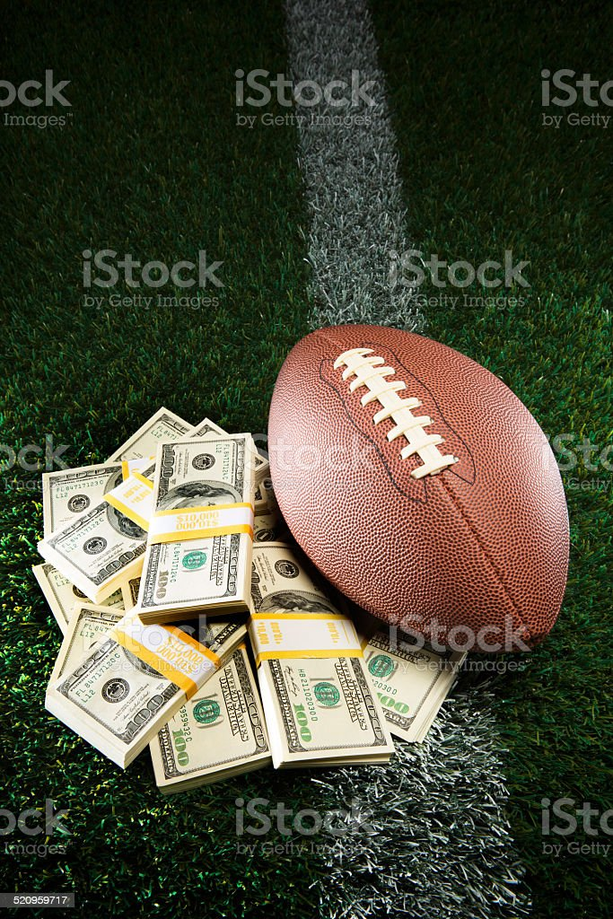 American Football Pile of Cash on Grassy Field stock photo