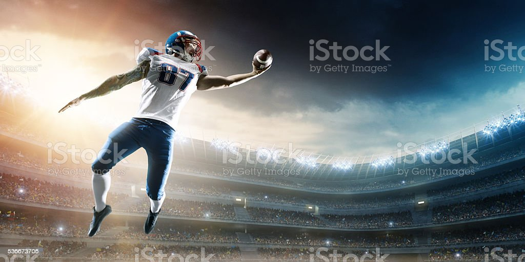 American football player catching ball mid air in stadium stock photo