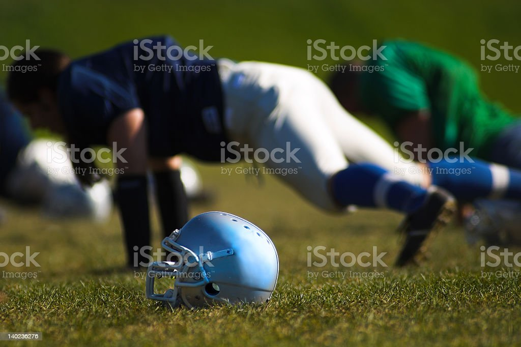 American football player does push up on grass beside helmet stock photo