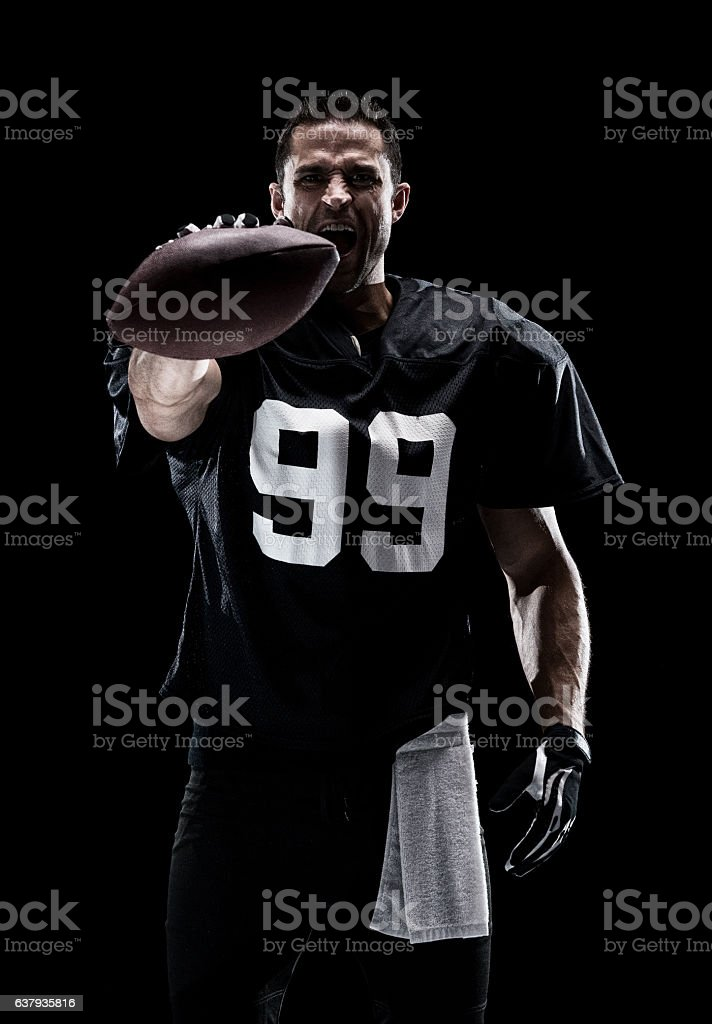 American football player holding ball stock photo