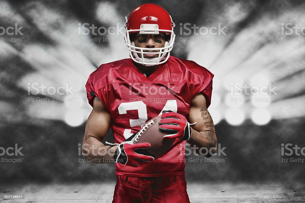 American football player in front of floodlight stock photo