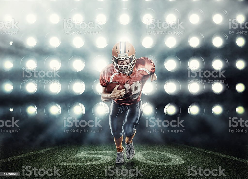 American football player in red uniform illuminated by floodlights stock photo